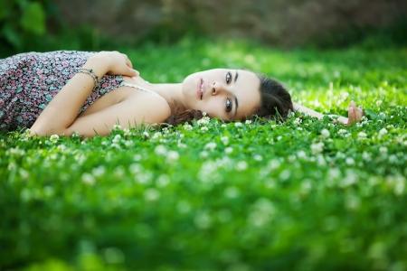 Jonge mooie Kaukasische vrouw neemt rust in park