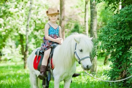 Meisjes maak een wandeling met pony Stockfoto