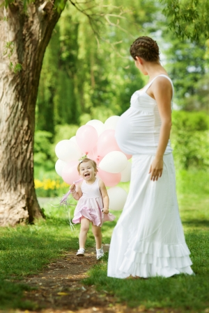 Pregnant mother and her daughter have fun outdoor photo