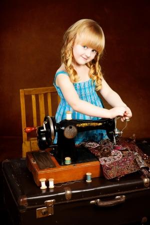 Vendimia que mira la foto de la chica joven trabaja en la m�quina de coser sobre fondo marr�n photo