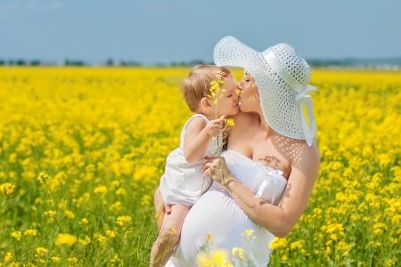 madre y bebe: Madre embarazada y su hija se divierten al aire libre