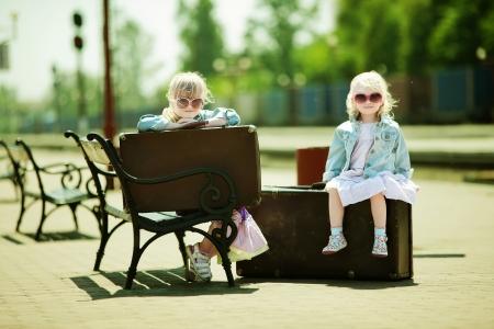 Vintage zoek foto van kleine meisjes met bagage op het station
