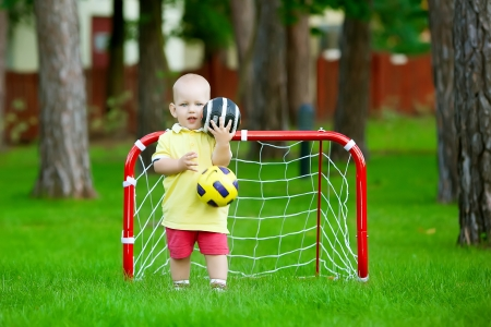 Small caucasian boy plays football in park  photo
