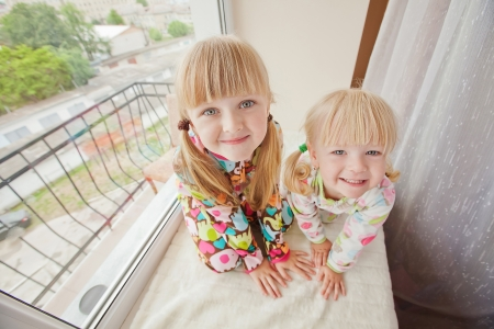 Two girls play at the windows-sill in pyjamas before sleep  photo
