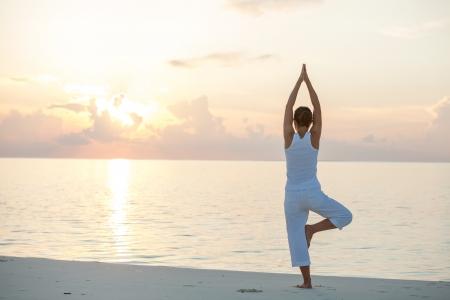 natural landscape: Caucasian woman practicing yoga at seashore
