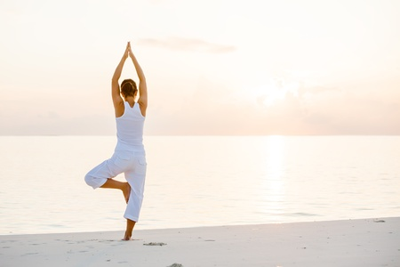 female pose: Caucasian woman practicing yoga at seashore