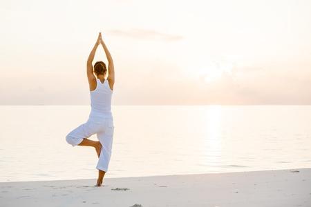 beach yoga: Caucasian woman practicing yoga at seashore