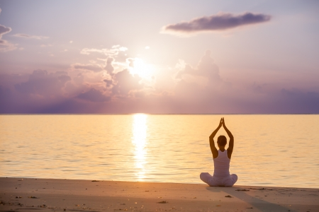 relaxation exercise: Caucasian woman practicing yoga at seashore