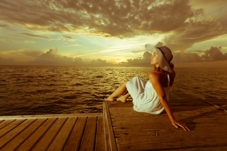 Caucasian woman takes rest at wooden pier to Indian ocean Stok Fotoğraf