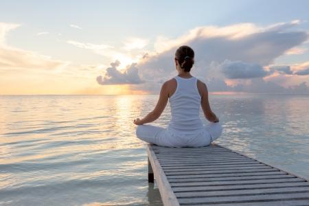 stile di vita: Caucasica donna praticare lo yoga in riva al mare