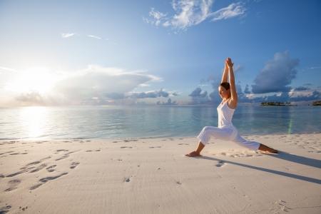 Caucasica donna praticare lo yoga in riva al mare Archivio Fotografico - 19868720