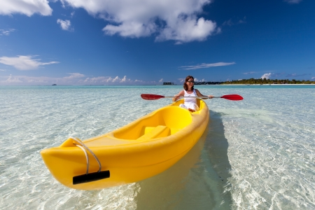 kayak: Young caucasian woman kayaking in sea at Maldives  Stock Photo