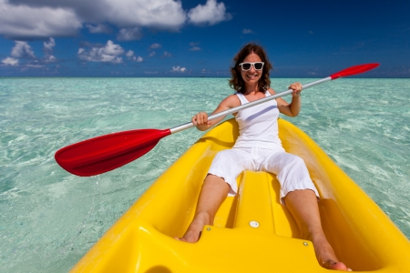 Young caucasian woman kayaking in sea at Maldives  版權商用圖片