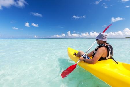 ocean kayak: Hombre joven cauc?sico kayak en el mar en Maldivas