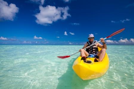 Jonge blanke man kajakken in zee in de Maldiven Stockfoto