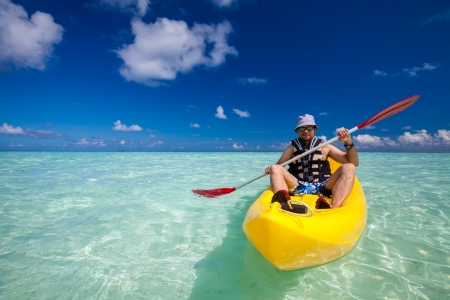 Young caucasian man kayaking in sea at Maldives  Stock Photo