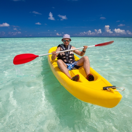 Young caucasian man kayaking in sea at Maldives  photo