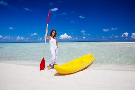 Young caucasian woman keeps paddle at the seashore near yellow kayak photo