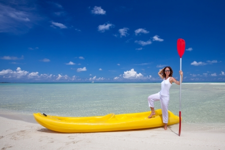 Young caucasian woman keeps paddle at the seashore near yellow kayak photo