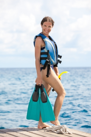 Woman prepares for snorkeling or diving with equipment for snorkeling in hands photo