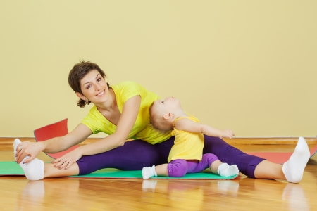 Mother do phisical exercises with her daughter at home Foto de archivo