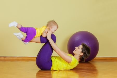 Mother do phisical exercises with her daughter at home Standard-Bild
