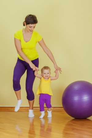 sporty: Mother do phisical exercises with her daughter at home Stock Photo