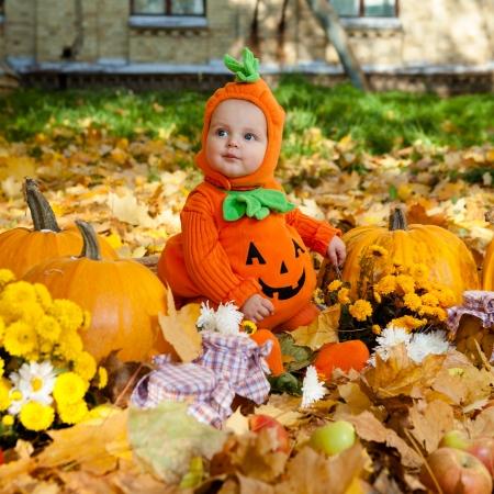 Child in Anzug Kürbis auf Hintergrund der Blätter im Herbst
