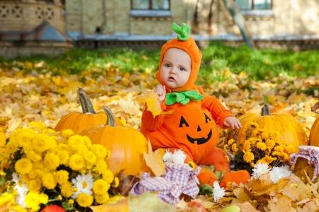 calabazas de halloween: Ni�o en traje de calabaza sobre fondo de hojas de oto�o Foto de archivo
