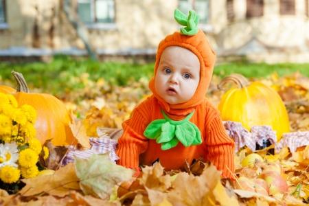 Child in pumpkin suit on background of autumn leaves 版權商用圖片 - 22011098