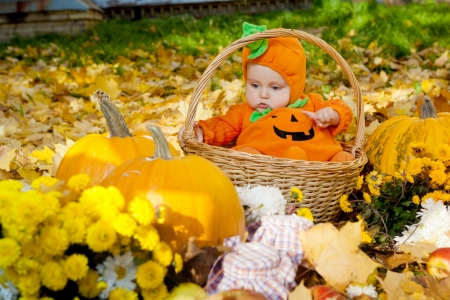 Child in pumpkin suit sitting in wooden basket on autumn leaves photo