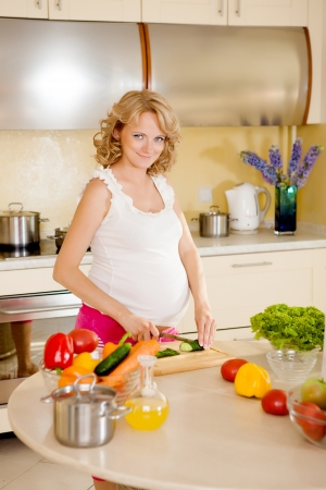 Pregnant woman prepares vegetable salad at home photo