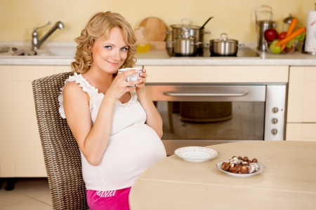 Young pregnant woman drinks tea with sweets at kitchen photo