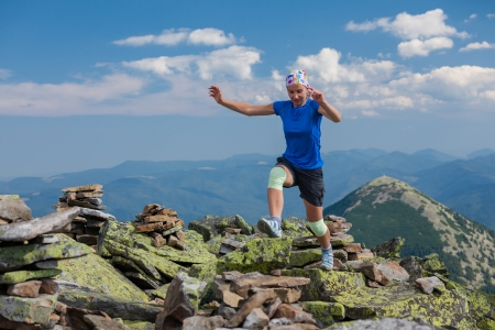 Woman athlete is jumping over stones in mountains photo