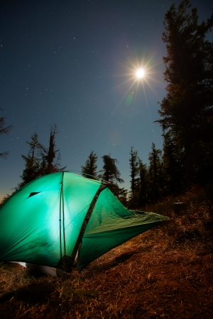 Tent illuminated with light in night forest photo
