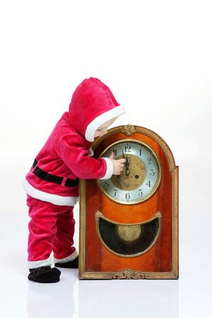 12 oclock: Small boy in Santa suit plays with vintage clock in white studio