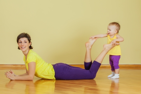 Mother do phisical exercises with her daughter at home Stock Photo