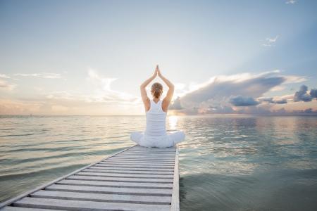 Caucasian woman practicing yoga at seashore