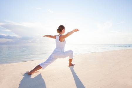 sunrise at the beach: Caucasian woman practicing yoga at seashore