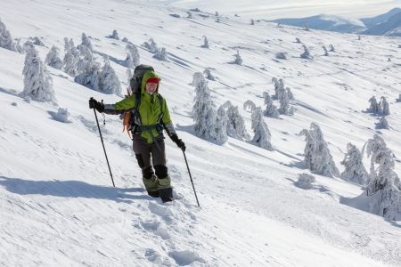 Hiker walking in winter Carpathian mountains photo