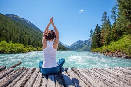 Jonge vrouw is het beoefenen van yoga op bergrivier