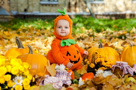 Child in pumpkin suit on background of autumn leaves photo