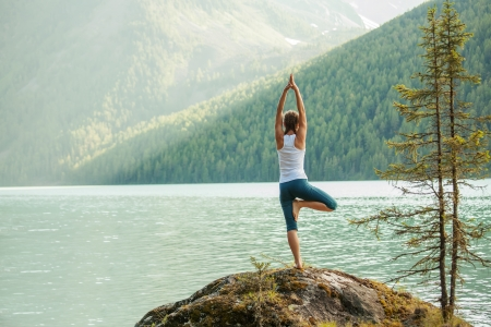 Young woman is practicing yoga at mountain lake Фото со стока - 22482185