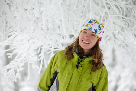 Young woman posing at camera in winter mountains photo