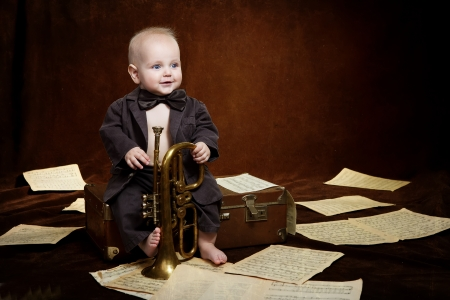 Caucasian baby boy plays with trumpet photo