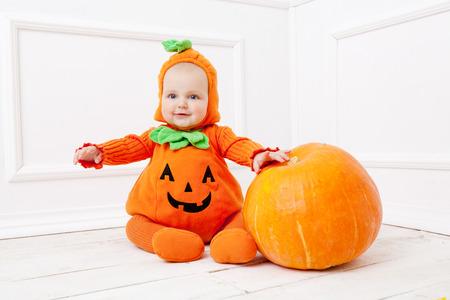 Child in pumpkin suit on white background with pumpkin