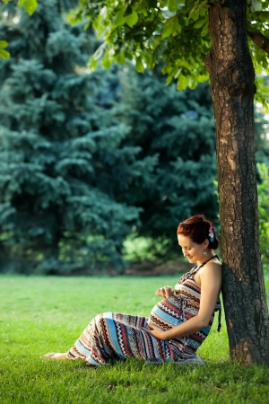 Pregnant caucasian woman takes rest outdoor photo