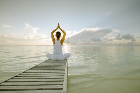 Caucasica donna praticare lo yoga in riva al mare Archivio Fotografico - 22485055