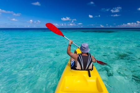 Blanke man kajakken in zee in de Maldiven Stockfoto