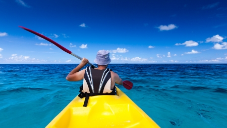 Caucasian man kayaking in sea at Maldives  photo